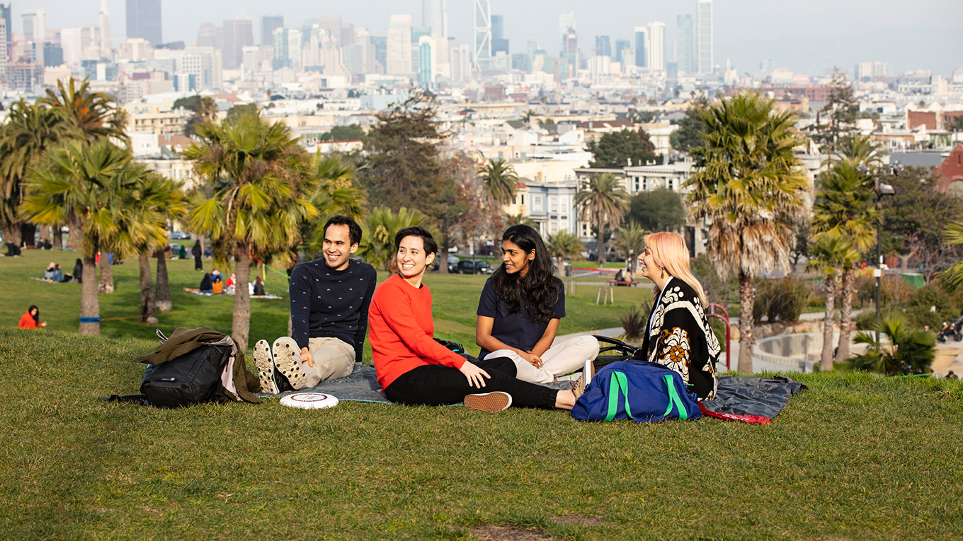 Employees in park with city skyline in the background